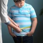 Kind mit Übergewicht wird gerade am Bauch gemessen