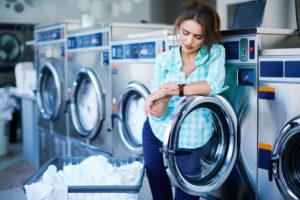 Frau steht an einer Waschmaschine im Waschsalon