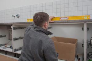 Mann misst Küchenschrank mit Wasserwaage nach