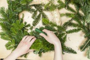 Händer befestigen Tannenzweige an Adventskranz