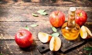Apfelessig und Äpfel auf einem Holztisch