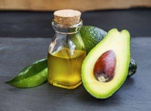 Als Naturkosmetik liegt eine Avocado mit Öl auf einem Tisch