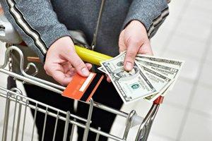 Hände halten Bargeld und Karte über einem Einkaufswagen im Supermarkt
