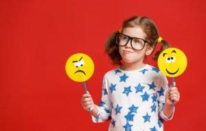 Kind mit Smileys an einem Stock, die Gefühle ausdrücken