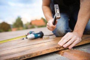 Mann bearbeitet Holzterrasse am haus