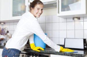 Frau putzt Küche mit dem Hausmittel Essig