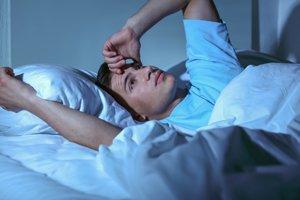 junger Mann schlaflos nachts im Bett