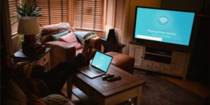 Mann streamt von Laptop auf Fernseher