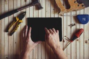 Tablet liegt mit Werkzeug auf Unterlage