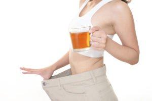 Schlanke Frau mit Tee zum Abnehmen