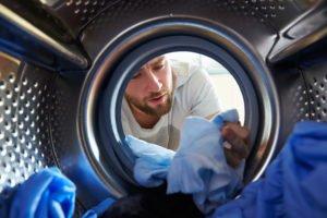 Mann will wäsche in Waschmaschine färben