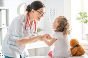 Ärztin untersucht Kind mit Teddybär