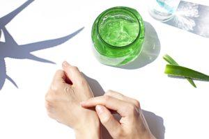 person cremt hand mit aloe vera gel ein