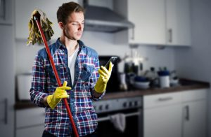 ein junger mann schaut beim putzen auf sein smartphone