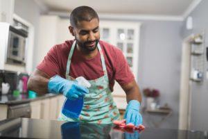 ein mann beim reinigen der kuechenarbeitsplatte aus marmor