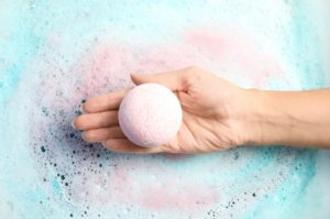 ein frau haelt eine badekugel in der hand
