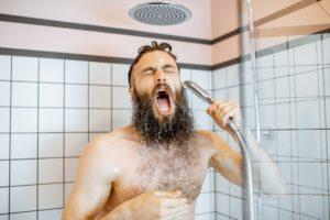 ein mann mit bart unter der dusche