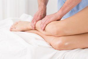 Physiotherapeut massiert Beine.