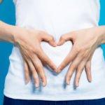 Frau formt ein Herz mit Ihren Händen auf Ihren Bauch