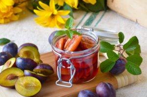 Obst in einem Glas, daneben andere Früchte und Blumen dekoriert