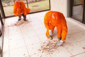 zwei handwerker entfernen einzelne fliesen in der kueche