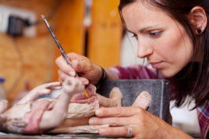eine frau restauriert eine figur aus porzellan