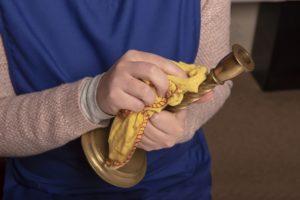 Frau reinigt Kerzenständer mit Tuch.