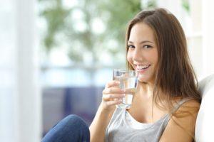 Frau hält ein Wasserglas