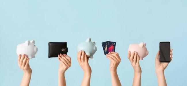 hände halten geldbörse, sparschwein, kreditkarten und handy