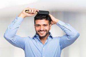 Mann kämmt zur Pflege seine Haare.