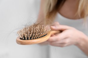 eine frau haelt eine haarbuerste mit haaren in der hand