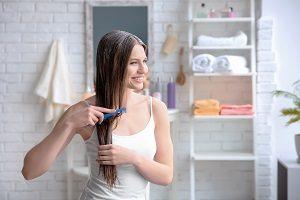 Frau bürstet ihre Haare.