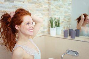 Frau stylt sich die Haare.