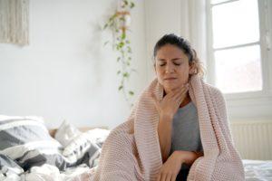 Frau in Bett mit Halsschmerzen