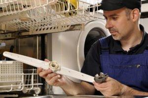 Handwerker reinigt Spülmaschine