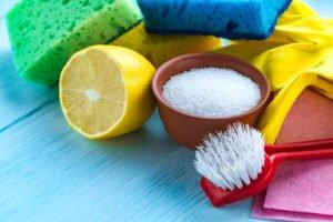Schwamm, Bürste, Zitrone und Salz auf einem Stapel