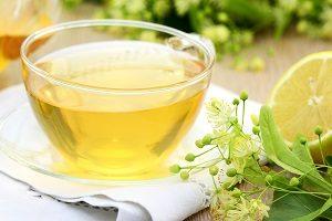 Eine Tasse Tee, drum herum Kräuter und eine Zitrone