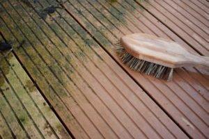 Holzterrasse mit Bürste reinigen