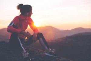 Joggerin macht auf einem Berg Pause