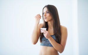 eine frau isst joghurt
