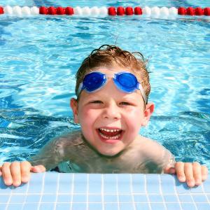 froehlicher junge im schwimmbecken