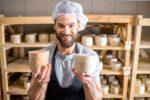 Mann hält Käse in der Hand.
