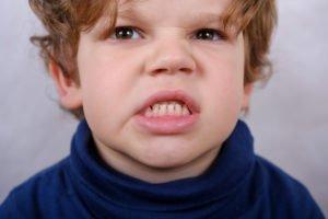 Kind zeigt wütend die Zähne