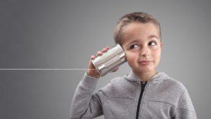 Junge mit Schnurtelefon auf einer Dose.