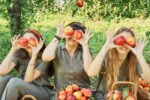 Kinder spielen mit Äpfeln von Apfelbaum