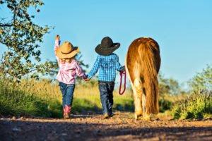 Junge und Mädchen laufen als Cowboy und Cowgirl verkleidet mit Ponny