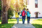 Kinder mit Rucksäcken vor der Schule