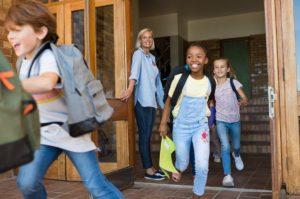 Kinder rennen lachend aus einer Schule