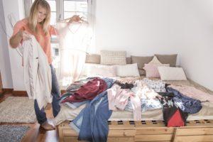 eine frau beim ausmisten des kleiderschranks