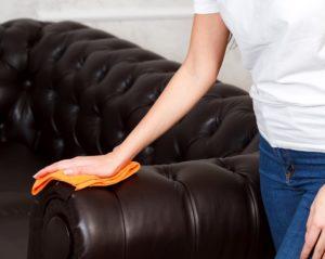 ein frau reinigt die couch aus kunstleder